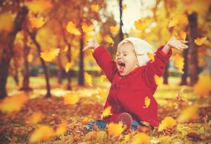 Child sitting and throwing leaves